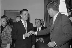 Two Knights of Columbus preside at the formation of the Peace Corps in 1961, as President John F. Kennedy hands a pen to brother-in-law Sargent Shriver after signing the bill that brought Shriver's brainchild into existence. (Photo: Bettmann/Corbis / AP Images)